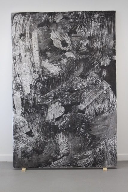 Black and white door size painting leaning against wall on painting blocks